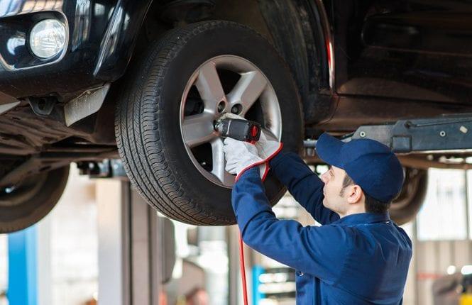 Portrait of a mechanic replacing wheel